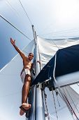 Young cheerful skipper on the yacht, strong handsome sailor on vessel, luxury lifestyle, traveling a