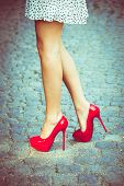 picture of short legs  - woman legs in red high heel shoes and short skirt outdoor shot on cobble street - JPG