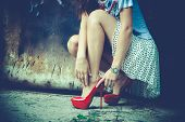 picture of squatting  - woman legs in red high heel shoes and short skirt outdoor shot against old metal door - JPG