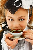 stock photo of mad hatter  - Beautiful tween girl in fantasy cosplay fashion sipping tea - JPG