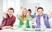 education concept - happy team of students showing thumbs up at school