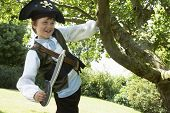 Boy in pirate costume swinging from tree in the park