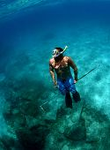 image of spearfishing  - a man with spear gun underwater in ocean - JPG