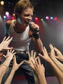 Young man singing on stage in concert close to adoring fans