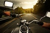 stock photo of driver  - Driver riding motorcycle on an asphalt road through forest - JPG