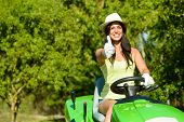 stock photo of tractor  - Successful and happy female gardener riding garden tractor doing approval gesture with thumbs up - JPG