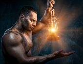 stock photo of kerosene lamp  - Photo of muscular man holding oil lamp - JPG