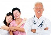 Smiling friendly Asian senior medical doctor and patient family. Woman health care concept. Isolated