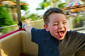 Happy child enjoying spinning ride at carnival with motion blur in background
