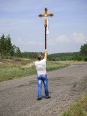 foto of glorify  - A man carries the cross of faith highly above a head on a road - JPG