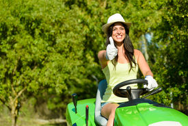 stock photo of grass-cutter  - Successful and happy female gardener riding garden tractor doing approval gesture with thumbs up - JPG