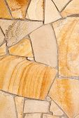 foto of porphyry  - Wall lined with light yellow porphyry stones - JPG