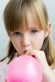Cute Little  Girl Inflating A Pink Balloon In The Kitchen