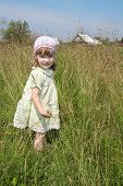 Pretty Little Girl In Dress Stands Among High Grass At Meadow At Summer Sunny Day