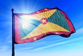 Grenada flag waving on the wind on the sky