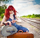 Beautiful woman with blue dress and suitcase on a train station.