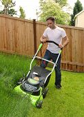 stock photo of grass-cutter  - Man cutting the grass with lawn mower - JPG