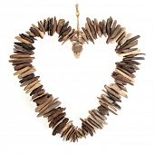 Driftwood love heart with small wooden pieces over white background.