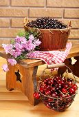 Fresh berries in baskets on wall background