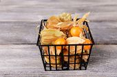 Physalis fruits in plastic basket, on wooden background