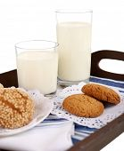 Milk and cookies on wooden tray isolated on white