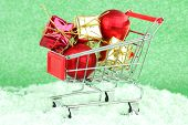 Christmas gifts in shopping trolley, on green shiny background