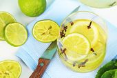 Fresh summer drink with lime and cloves in glass, on color wooden background