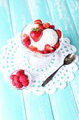 Creamy ice cream with raspberries on plate in glass bowl, on color wooden background