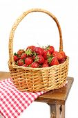 Fresh strawberries in basket on white wall background