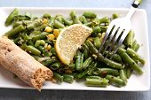 Salad with green beans and corn, sesame seeds on plate, on color wooden background