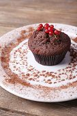 Chocolate muffin with red currant on plate on wooden background