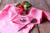 Chocolate ice cream with mint leaf and ripe berries in glass bowl, on color wooden background