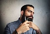 stock photo of barber  - Portrait of a man grooming his beard with scissors - JPG