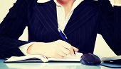 A photo of business woman writting in  her notebook.