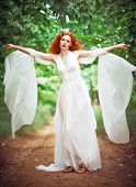 Beautiful Redhead Woman Wearing White Dress In A Garden