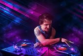 Attractive young DJ playing on turntables with color light effects