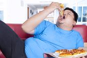 Obese Person Bite A Slice Of Pizza