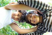 stock photo of love-making  - Two kids making a circle of trust and love - JPG