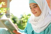 image of hijabs  - Beautiful Muslim girl reading book with hijab and smiling - JPG
