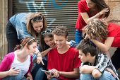 Smiling young people looking at a tablet computer on the street