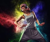 Stylish teenage girl with headphones dancing against colourful powder explosion