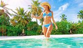 Cute slim female wearing stylish blue swimsuit comes into sea, enjoying summer vacation on Maldives
