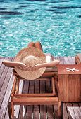 Luxury female tanning on the beach, wearing big stylish hat, enjoying beautiful seascape, summer tra