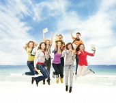 Group of smiling teenagers jumping together over the beach and sea background