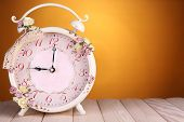 Beautiful vintage alarm clock with flowers on wooden table, on yellow background