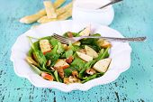 Green salad with spinach, apples, walnuts and cheese on color wooden background