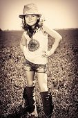 Pretty little girl on a meadow in summer day. Happy childhood. Wild west style, jeans.