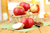 Ripe apples with with cinnamon sticks  on  wooden table, on bright background