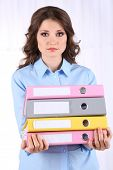Young business woman with office folders in room