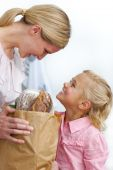 Smiling Mother And Her Daughter Unpacking Grocery Bag